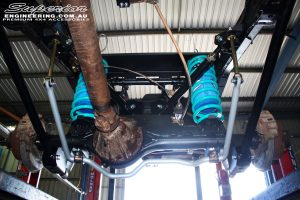 Middle rear underbody shot looking at the fitted Superior 79 Series Coil Conversion with Superior Sway Bar Kit, Dobinson Coil Springs, Airbag Man Coil Air Helper Kit, Tough Dog Adjustable Rear Shocks & Upper & Lower Control Arms