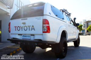 """Rear right view of a Toyota Vigo Hilux Dual Cab in White after fitment of a Superior Remote Reservoir 4"""" Inch Lift Kit with King Springs"""
