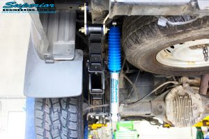 Rear left close up underbody view of the fitted Superior Nitro Gas Shock with Leaf Spring, Extended Shackle & U-Bolt Kit