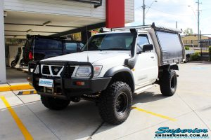 Left front side view of a Nissan GU Patrol Ute in White On The Hoist @ Superior Engineering Deception Bay Showroom