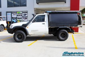 Left side view of a Nissan GU Patrol Ute in White On The Hoist @ Superior Engineering Deception Bay Showroom
