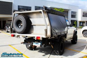 Rear right view of a Nissan GU Patrol Ute in White On The Hoist @ Superior Engineering Deception Bay Showroom