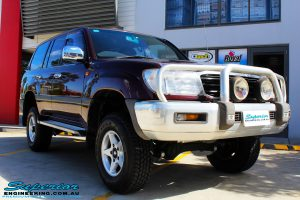 """Right front side view of a Maroon Toyota 105 Series Landcruiser Dual Cab after fitment of a Superior Nitro Gas 3"""" Inch Lift Kit with Airbag Man 3"""" Coil Air Kit"""