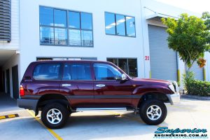 """Right side view of a Maroon Toyota 105 Series Landcruiser Dual Cab after fitment of a Superior Nitro Gas 3"""" Inch Lift Kit with Airbag Man 3"""" Coil Air Kit"""