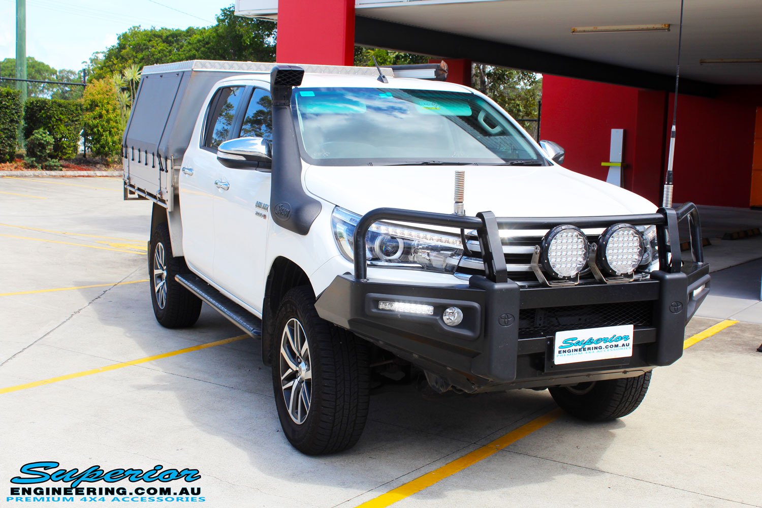 Right front side view of a White Toyota Revo Hilux Dual Cab being fitted with a Brown Davis 145L Long Range Fuel Tank @ Superior