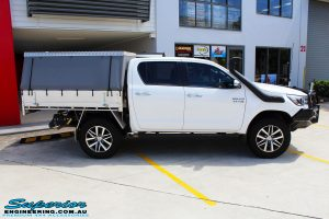 Right side view of a White Toyota Revo Hilux Dual Cab being fitted with a Brown Davis 145L Long Range Fuel Tank @ Superior