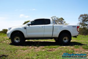 """Left side view of a White Ford PXII Ranger Dual Cab after fitment of a Superior 2"""" Inch Rear PXII Ranger Coil Conversion Kit with Redarc Dual Battery Setup"""