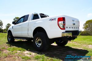 """Rear left side view of a White Ford PXII Ranger Dual Cab after fitment of a Superior 2"""" Inch Rear PXII Ranger Coil Conversion Kit with Redarc Dual Battery Setup"""