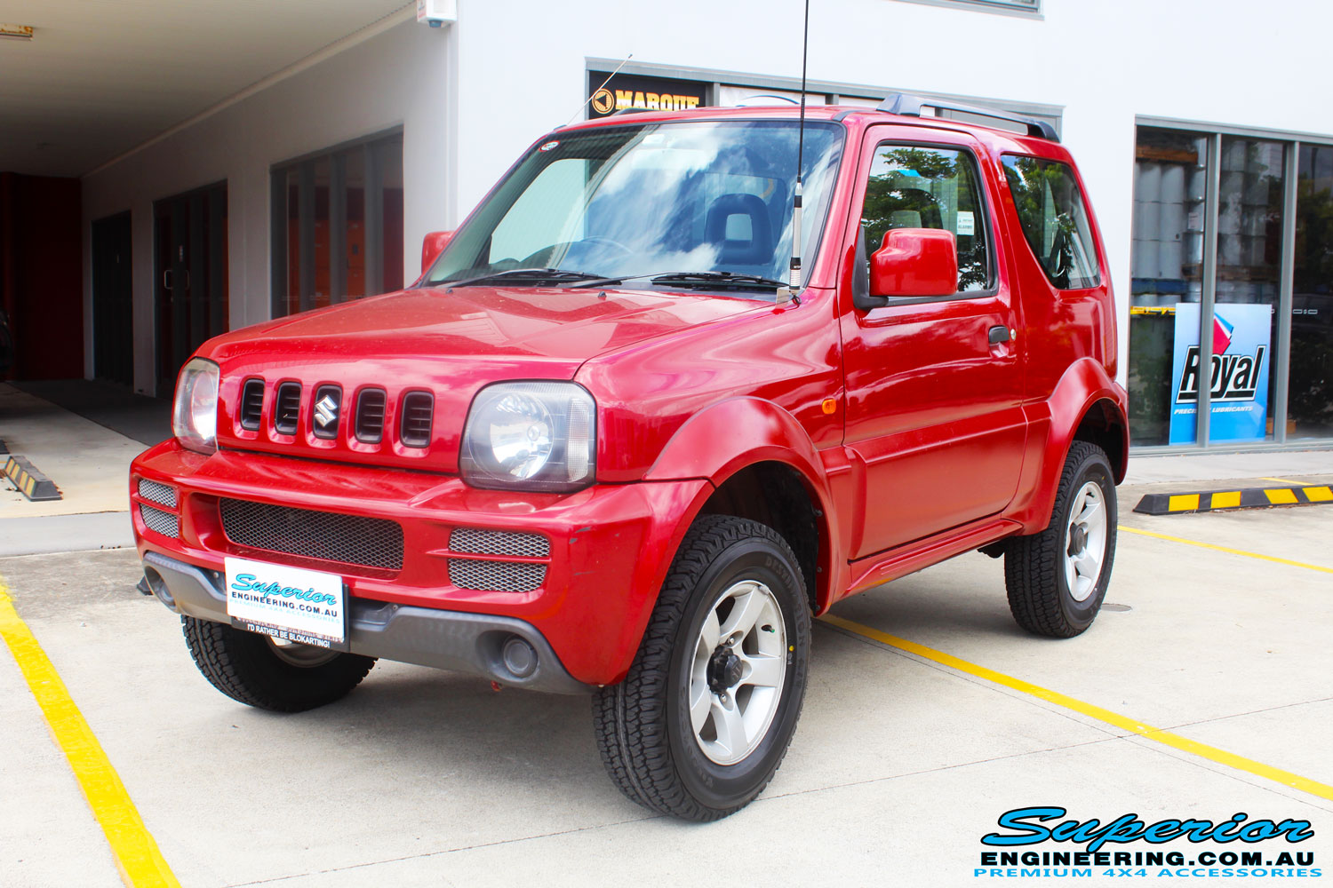 "Left front side view of a Suzuki Jimny in Red after fitment of a EFS 2"" Lift Kit"