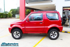 """Left side view of a Suzuki Jimny in Red after fitment of a EFS 2"""" Lift Kit"""
