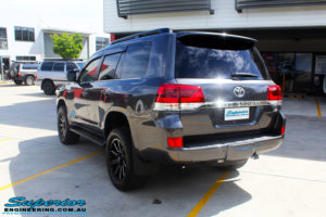 """Rear left side view of a Grey Toyota 200 Series Landcruiser after fitment of a Superior Remote Reservoir 2"""" Inch Lift Kit with King Springs & Airbag Man 2"""" Coil Air Helper Kit"""